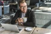 pohledný mladý freelancer s šálkem kávy a přenosný, posezení v kavárně