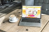 cup of cappuccino and laptop with aliexpress website on screen on rustic wooden table at cafe