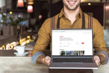 cropped shot of smiling young waiter holding laptop with airbnb website on screen in cafe
