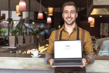 handsome young waiter holding laptop with google website on screen in cafe