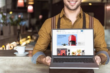 cropped shot of smiling young waiter holding laptop with ebay website on screen in cafe