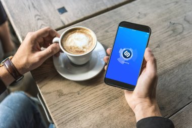 cropped shot of man with cup of cappuccino using smartphone with shazam app on screen