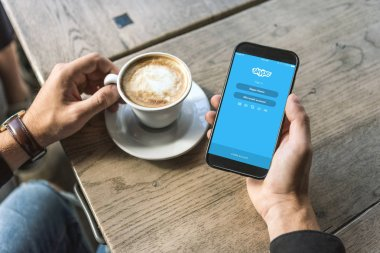 cropped shot of man with cup of cappuccino using smartphone with skype app on screen