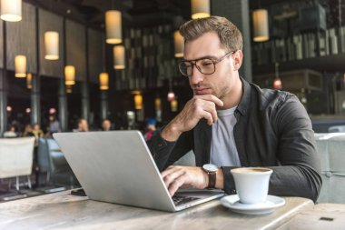handsome young freelancer working with laptop in cafe with cup of coffee on table