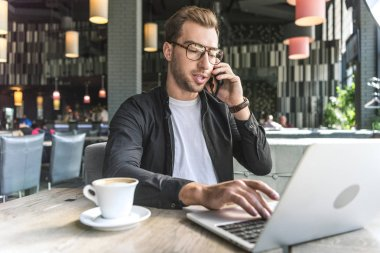 handsome young freelancer with cup of coffee working with laptop in cafe and talking by phone