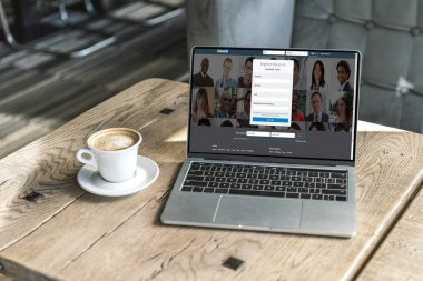 cup of coffee and laptop with linkedin website on screen on rustic wooden table at cafe