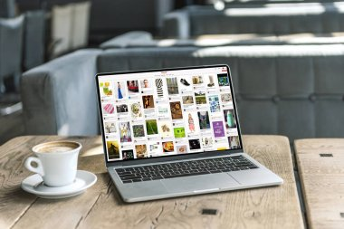 cup of coffee and laptop with pinterest website on screen on rustic wooden table at cafe
