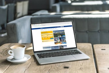 cup of coffee and laptop with booking website on screen on rustic wooden table at cafe