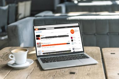 cup of coffee and laptop with soundcloud website on screen on rustic wooden table at cafe