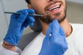 abgeschnittene Aufnahme einer Zahnärztin, die Zähne einer glücklichen Kundin untersucht