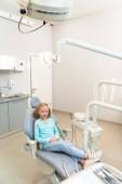 Fotografie vysoký úhel pohled roztomilé malé dítě sedí v Zubařské křeslo v ordinaci