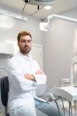 pohledný mladý zubař s překřížením rukou při pohledu na fotoaparát v úřadu