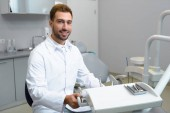 smiling young dentist in white coat looking at camera in office
