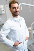 handsome young dentist in white coat looking at camera in office