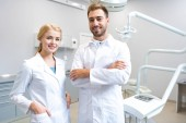 young male and female dentists looking at camera in dental office