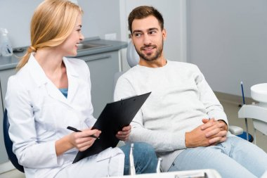 female dentist with clipboard and client looking at each other in dentist office