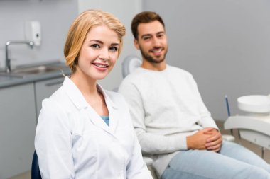 smiling female dentist and handsome young client looking at camera in dentist office
