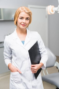 beautiful young dentist with clipboard standing in office