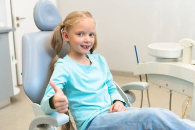 beautiful little child sitting in dental chair at dentist office and showing thumb up