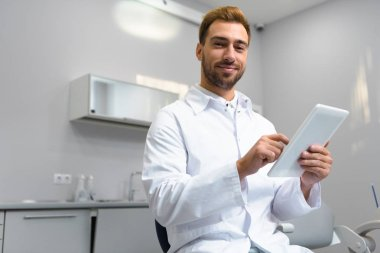 handsome young dentist in coat using tablet in office