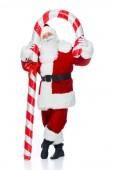 Happy santa claus stojí s velkou vánoční cukrové třtiny izolované na bílém