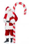 Santa claus stojí s velkou vánoční cukrové třtiny izolované na bílém
