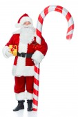 Fotografie Weihnachtsmann stehend mit großen Candy Cane und Weihnachten Geschenk isoliert auf weiss