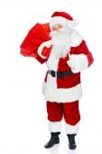 Santa claus s červenou vánoční taška ukazuje palcem izolované na bílém