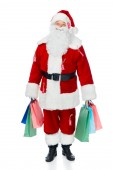 Fotografie happy santa claus in red costume with sale tags holding shopping bags isolated on white