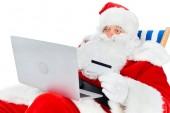 Fotografie Happy santa claus online nakupování s notebookem a kreditní karty při posezení na pláži židli izolované na bílém