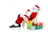 Fotografie Santa Claus holding Heißgetränk und auf Strandkorb sitzend mit Weihnachtsgeschenke auf weiß