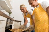 Fotografie low angle view of happy grandmother and granddaughter putting baking tray with cookies in oven