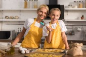 happy grandmother and granddaughter in aprons smiling at camera while preparing cookies together