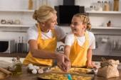 Fotografie šťastná babička a vnučka v zástěry se navzájem při přípravě souborů cookie dohromady