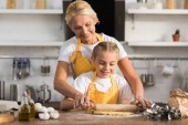 happy grandmother and granddaughter preparing dough together in kitchen