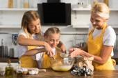 Fotografie rozkošný šťastné dítě s matkou a babičkou, příprava těsta spolu v kuchyni