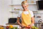 krásná zralá žena v zástěře vaření zeleninový salát v kuchyni