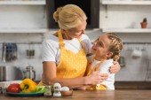 happy grandmother and granddaughter hugging and smiling each other while cooking together