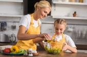 Fotografie šťastná babička a vnučka v zástěry společné vaření