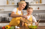 happy grandmother and granddaughter in aprons cooking together in kitchen