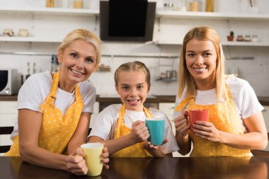 beautiful happy three generation family in aprons holding colorful cups and smiling at camera