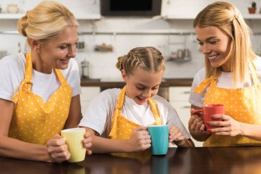 happy family of three generations in aprons holding colorful mugs in kitchen