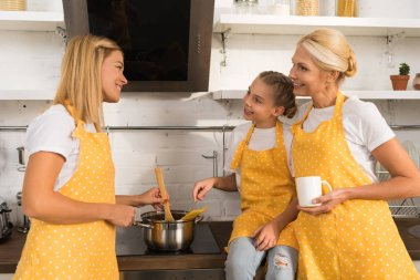 happy family in aprons smiling each other while cookies together in kitchen