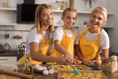 Cute happy kid with mother and grandmother smiling at camera while preparing cookies together stock vector