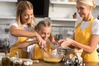 adorable happy child with mother and grandmother whisking eggs and preparing dough together