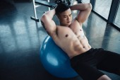 Fotografie young sportsman with bare chest doing abs exercise on fitness ball at gym