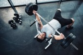 Fotografie top view of concentrated sportsman training with barbell at gym