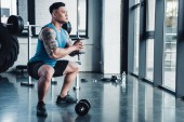 Fotografie concentrated young sportsman exercising with dumbbells in gym