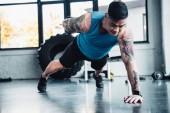 Fotografia giovane sportivo facendo una plancia di braccio allenarvi in palestra