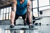 Fotografie young sportsman exercising with dumbbells in gym on sport mat